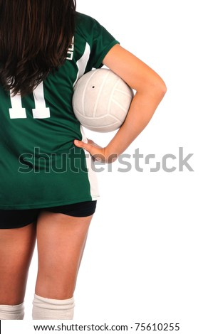 Female Volleyball player seen from behind holding a ball in the crook of her arm and held against her body. She is set to one side of the frame only showing knees to shoulder.