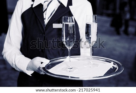 Female waiter welcomes guests with champagne, toned image - stock photo