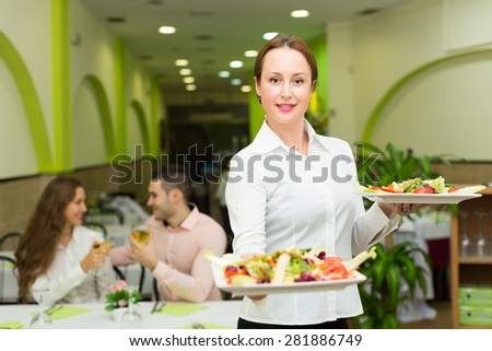 Female waiter with plates in hands serving guests table in restaurant - stock photo