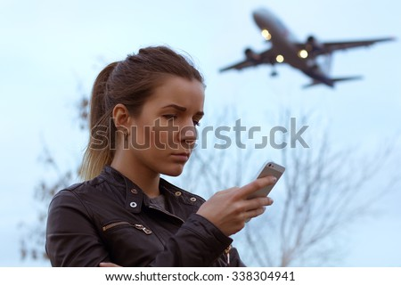 Female waiting on airport platform using her smartphone device. Landing airplane on background. Evening light. Vintage toned. - stock photo