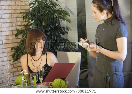 female waitress takes order in a restaurant - stock photo