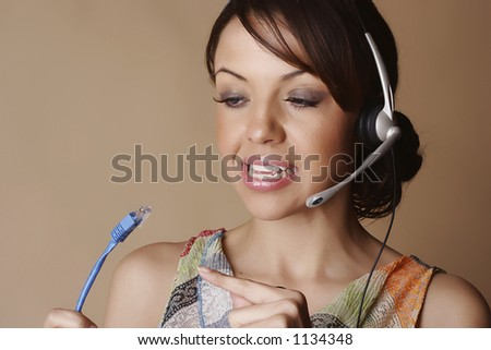 Female wearing a headset and pointing to a network cable - stock photo