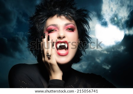 Female werewolf. Beautiful young woman screaming with fangs, wolf lenses and decorated nails. Halloween concept - stock photo