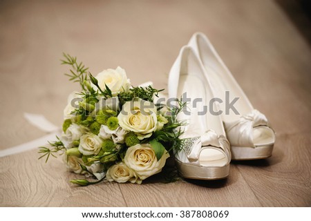 Female white silk wedding shoes with bride's bouquet of white roses flowers on wooden background. - stock photo