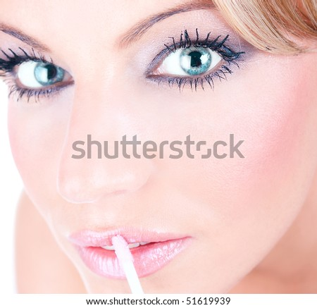 Female with beautiful makeup applies a slick of pink lip gloss to lips