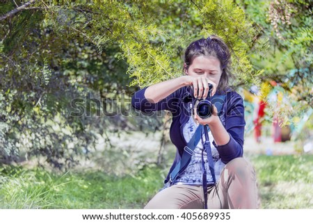 Female with camera taking a picture in a park on sunny day - stock photo