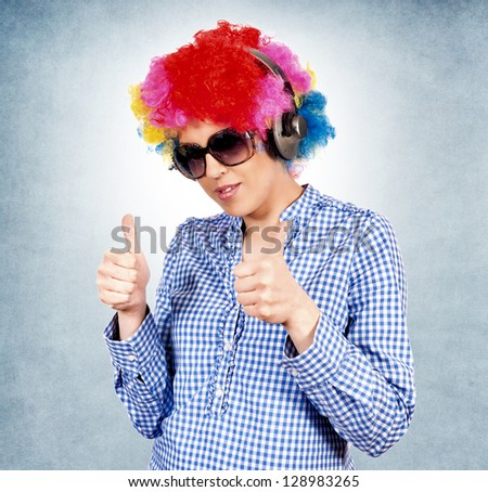 Female with clown wig and headphones showing ok sign with her fingers