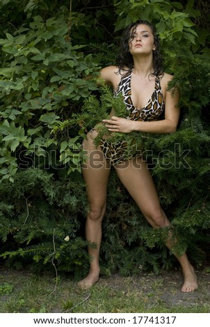 Female with dark hair posing in a 1 piece bathing suit outside - stock photo