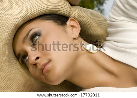Female with green eyes poses in white with a cream hat and white earrings - stock photo