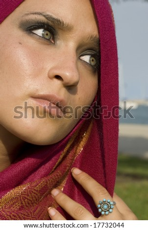 Female with green eyes staring in the distance with a fuchsia head scarf - stock photo