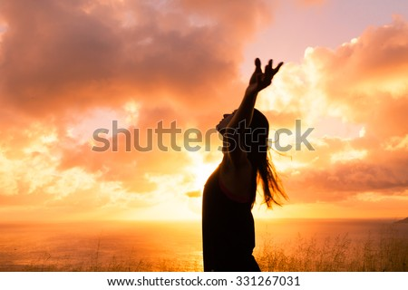 Female with her hand up in the air looking into the sky.  - stock photo