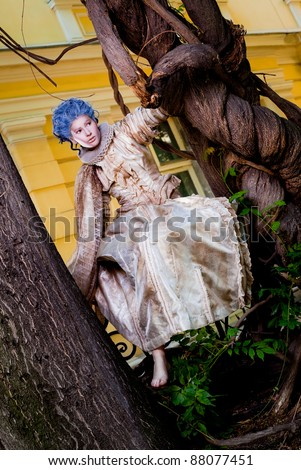 Female with medieval dress and blue wig sitting barefoot on a fence