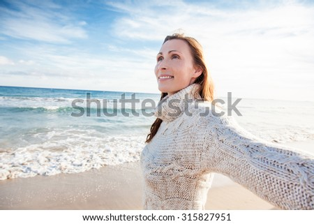 female with outstretched arms on the beach - stock photo