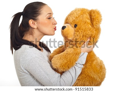 Female with pigtails kissing teddy bear isolated on white background - stock photo