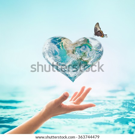 Female woman hands reaching up green planet w/ butterfly drinking water from the globe on turquoise aqua blue color water background : World ocean csr concept: Element of this image furnished by NASA - stock photo