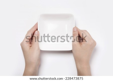 Female(woman) two hands hold a white bowl(plate) isolated white and top view. - stock photo