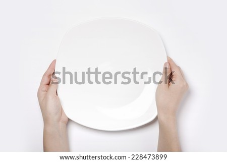 Female(woman) two hands hold a white dish(plate) isolated white and top view. - stock photo