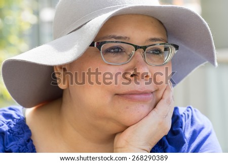 Female woman with cancer avoids skin reactions to chemo treatment by wearing hat - stock photo