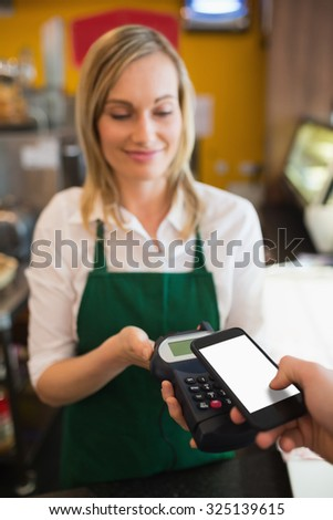 Female worker accepting payment from customer through NFC in bakery - stock photo