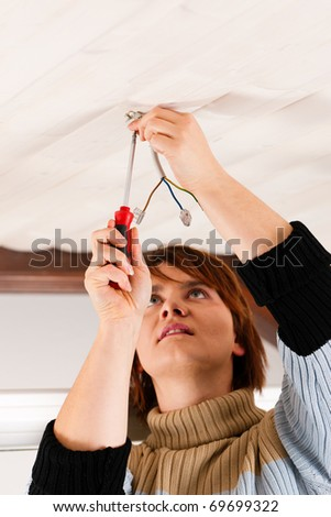 Female worker doing work on electrical installation - stock photo