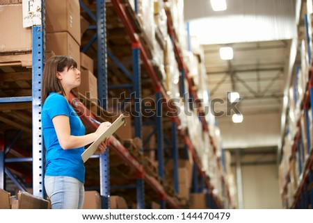 Female Worker In Distribution Warehouse - stock photo