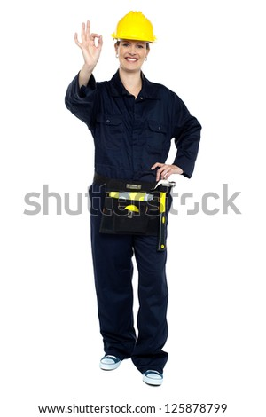 Female worker in jumpsuit showing perfect gesture. Work is good. - stock photo