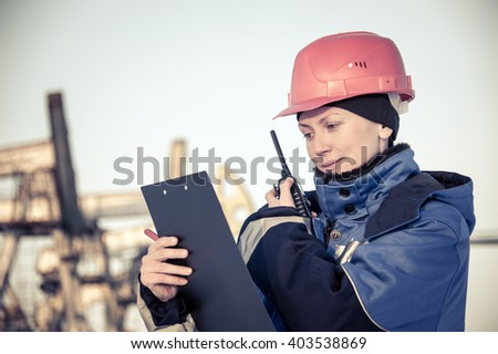 Female worker in the oil field talking on the radio wearing red helmet and blue work clothes. Industrial site background. Toned. - stock photo