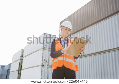 Female worker reading clipboard in shipping yard - stock photo