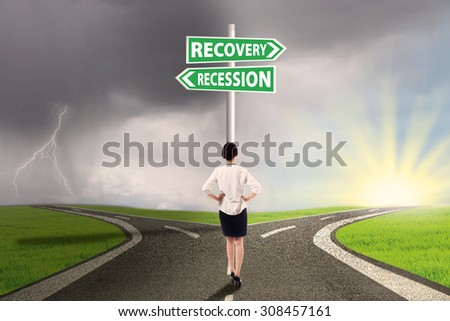 Female worker standing on the road and look at the signpost pointing on the road to recovery or recession finance - stock photo