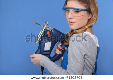 Female worker with a jigsaw - stock photo