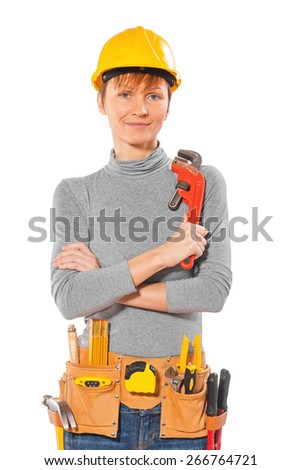 female worker with tools in tolbelt holding monkey wrench and looking at camera isolated