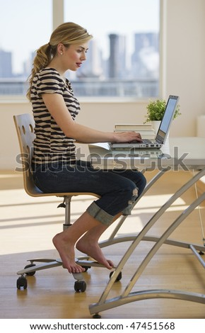 female working on laptop at home office - stock photo