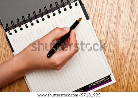 female writing in the organizer on a wooden table
