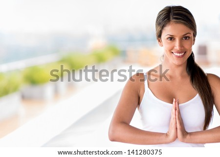 Female yoga instructor with hands together and smiling - stock photo