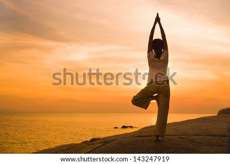 female yoga silhouette  on beautiful beach during sunset