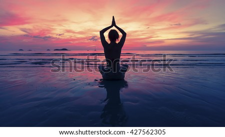 Female yoga silhouette on the beach after sunset. - stock photo