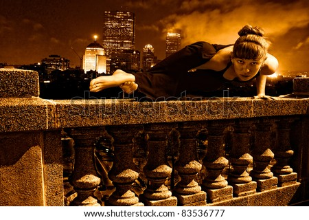 Female Yoga super hero doing arm balance on top of skyscraper cement balustrade, boston skyline is in the distance behind her with smoke