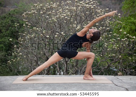 Female yoga teacher executing postures (asanas) at an old hotel in Rishikesh, India. - stock photo