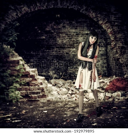 Female zombie with blood holding knife in ruins - stock photo