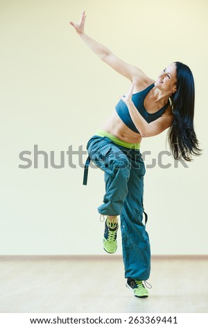 female zumba instructor doing dancing exercises in sport club - stock photo