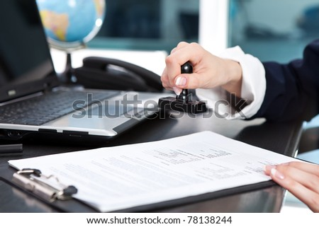 females hand putting stamp on a document, close up - stock photo