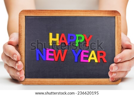 Females hands showing black board against new year greeting - stock photo