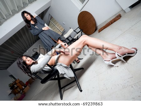 Females in studio backstage, one of them leaning on chair, the other standing - stock photo