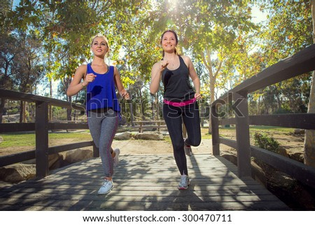 Females jogging to stay fit exercise cardio outdoor natural park nature setting on beautiful day - stock photo