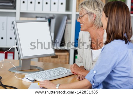 Females of different generations looking at the computer, working together in the office. - stock photo