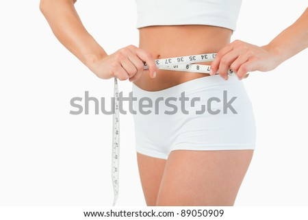 Feminine body with a measuring tape against a white background - stock photo