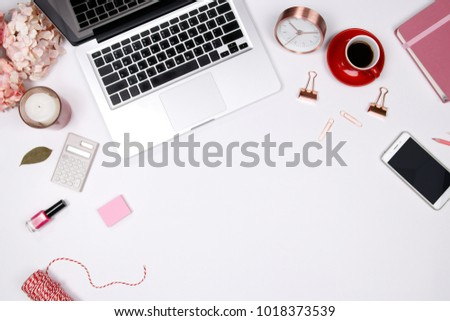 Feminine desk workspace frame with pink beige floral bouquet, red coffee cup, smartphone accessories and notebook on white background with copy space. Flat lay. Top view. Valentines day background.