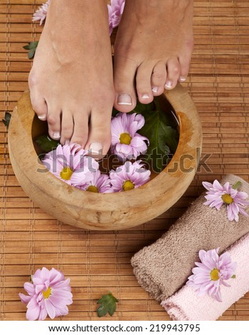 Feminine feet and foot spa bowl with flowers and towels - stock photo