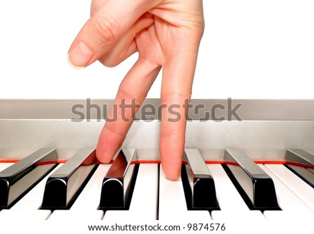 Feminine hand fingers walking along a piano keyboard - stock photo