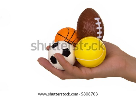 Feminine hand holding miniaturized rubber sport balls over white background - stock photo